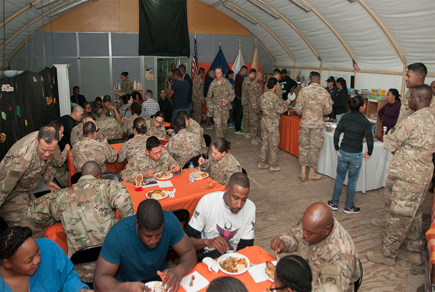 U.S. Soldiers of the 369th Sustainment Brigade eat a Thanksgiving holiday meal at Camp Arifjan, Kuwait, Nov. 26, 2016.