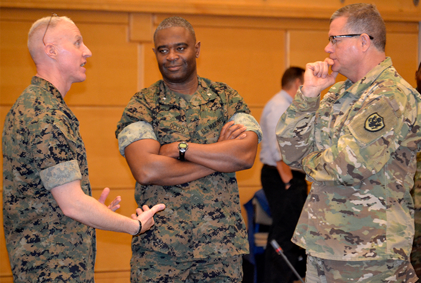 "Marine Corps Lt. Col. Adam Blanton and Col. Seth Ocloo from the Marine Corps Warfighting Laboratory discuss future sustainment with DLA Troop Support Commander Army Brig. Gen. Mark Simerly, pictured left to right, during a Campaign of Learning ""Future of Warfare"" event March 21, 2019 in Philadelphia."