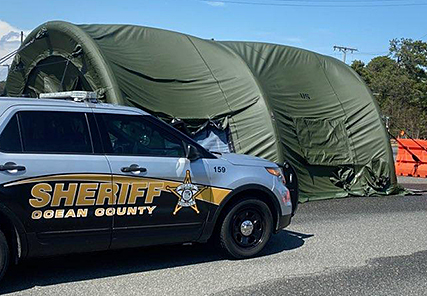A sheriff's vehicle and a military tent