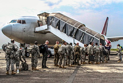 An image of service members in a line boarding a plane