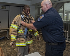 Hish school student tries on a firefighter uniform