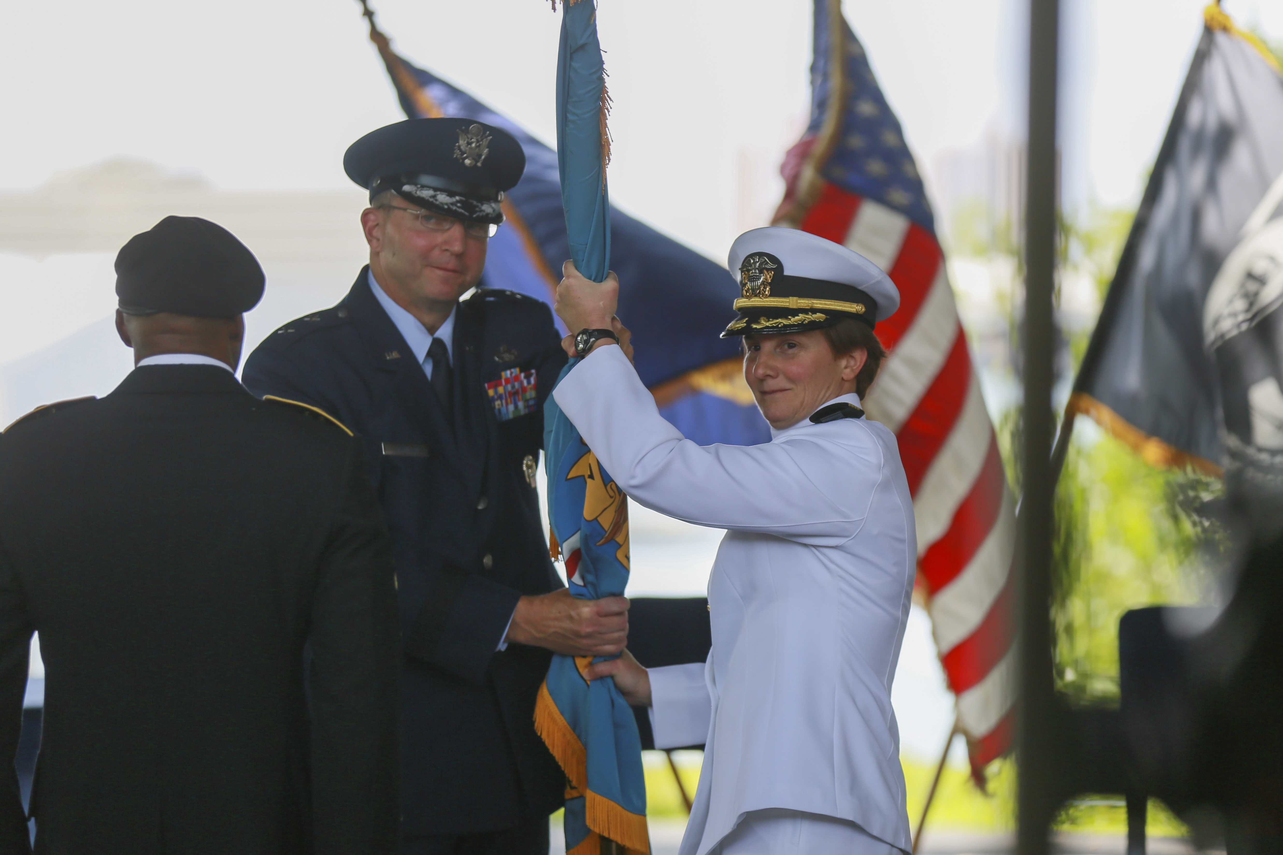 Air Force major general passing official flag to Navy captain, both in Class A uniforms