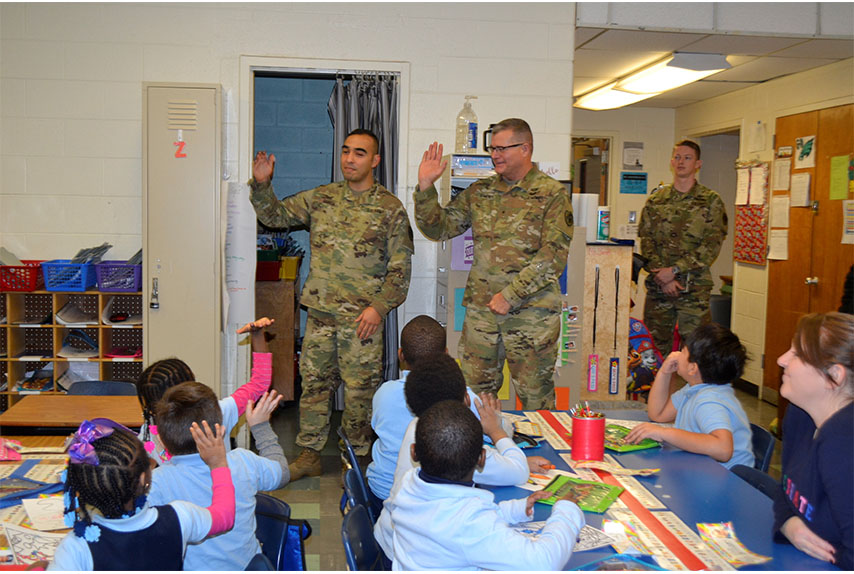 Army Chief Warrant Officer 3 Eugene Garcia, left, Brig. Gen. Mark Simerly, DLA Troop Support commander, middle, and 1st. Lt. Riley Kramer, DLA Troop Support Aide-de-Camp, right, greet students during the Children's Holiday Party at Benjamin Franklin Elementary School Dec. 6, 2018 in Philadelphia.