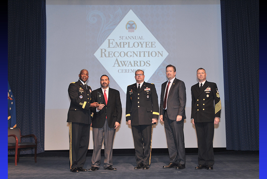 DLA Director Army Lt. Gen. Darrell Williams, left, DLA Troop Support Commander Army Brig. Gen. Mark Simerly, center, and Navy Command Master Chief Shaun Brahmsteadt (far right) present Roberto Santana Irizarry, second left, contracting officer representative, DLA Troop Support Subsistence supply chain, with the DLA Leader of the Year award during the 51st Annual Employee Recognition Awards Ceremony, Dec. 13, 2018 at the McNamara Headquarters Complex Auditorium, Ft. Belvoir, Va.