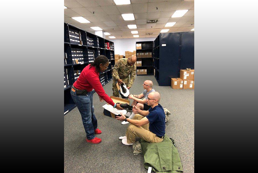 Air Force clothing initial issue section chief Vernalynne Carter and 502nd Logistics Readiness Squadron Commander Air Force Lt. Col Ernest Cage issue new American-made athletic footwear to Air Force recruits Daniel Sterling, right, and Ryan Padro, second right, at Joint Base San Antonio-Lackland, Texas, Jan. 3, 2019.