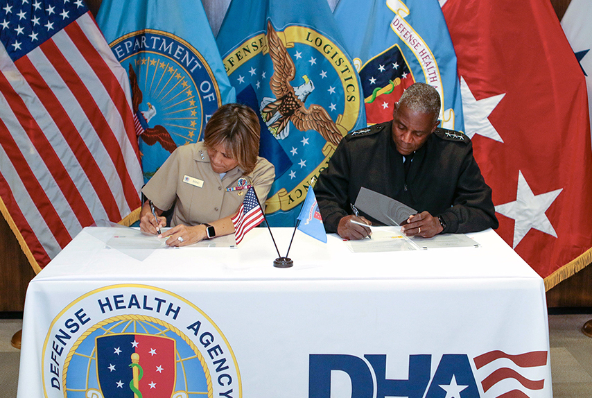 Navy Vice Adm. Raquel Bono, DHA Director, left, and Army Lt. Gen. Darrell K. Williams, DLA Director, right, sign a memorandum of agreement Aug. 15, 2019 at the DHA headquarters in Falls Church, Virginia.