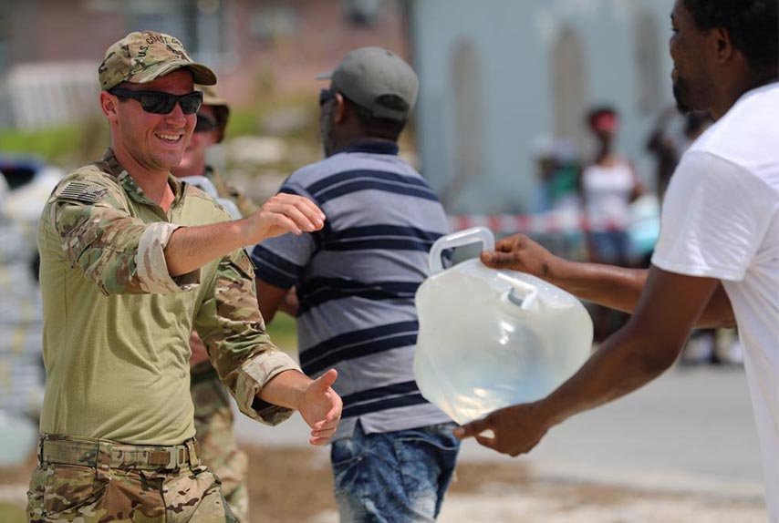 A U.S. Coast Guardsman provides water to those affected by Hurricane Dorian in the Bahamas, Sept. 8, 2019. DLA Troop Support provided more than 1,400 cases of bottled water to various Department of Defense customers in support of the hurricane relief efforts.