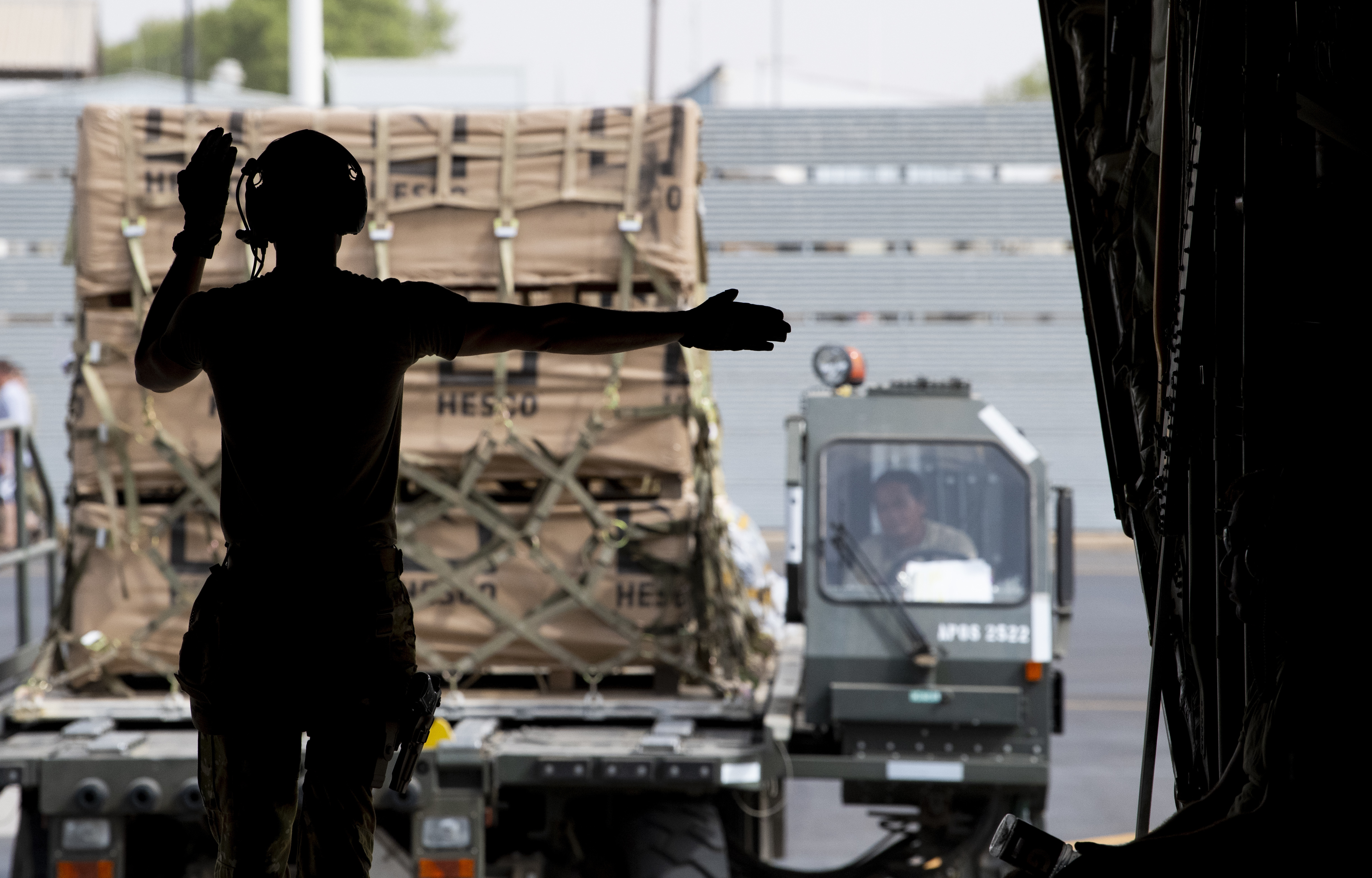 A service member directs material handling equipment loaded with cargo onto the ramp of an aircraft.