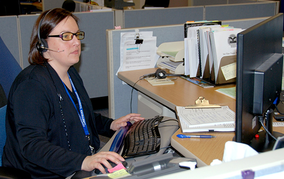 A DLA employee sits at her computer while assisting a customer over the phone, linking to the Place An Order page