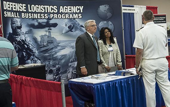 Two DLA Small Business employees speak to a customer at a booth labeled 'Defense Logistics Agency Small Business Programs,' links to the DLA Small Business page