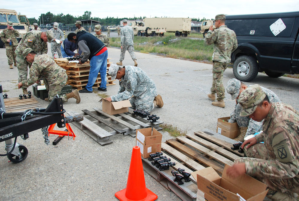 Service members receive assistance turning in equipment on pallets