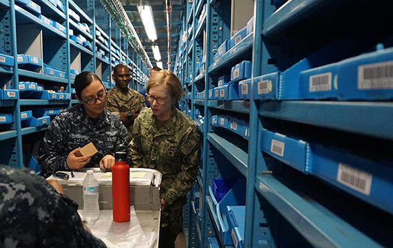 Several military service members brows inventory bins in a warehouse, linking to the What's Available At DLA page