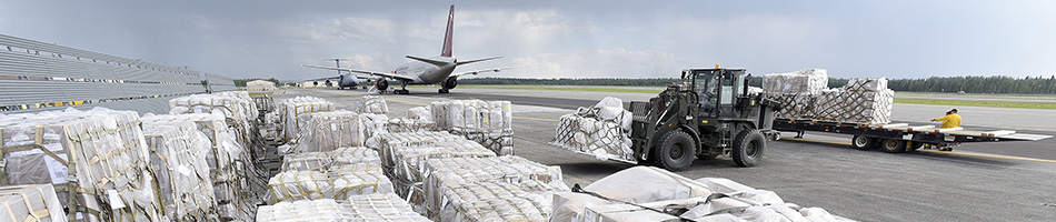 Wrapped pallets of cargo sitting in an airfield are loaded into a plane