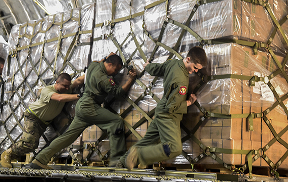 Three military service members push a wrapped pallet of equipment, linking to the Where's My Stuff page