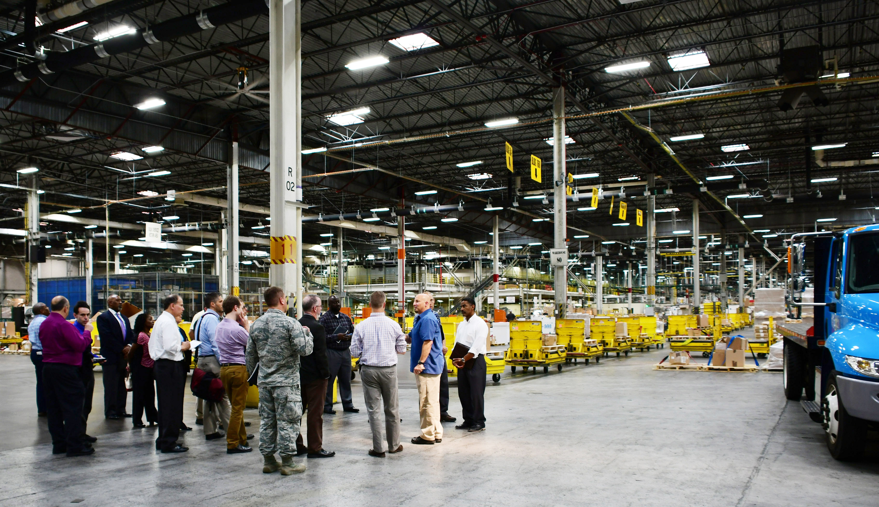 A group is gathered in a warehouse, showing the expanse of the warehouse behind them