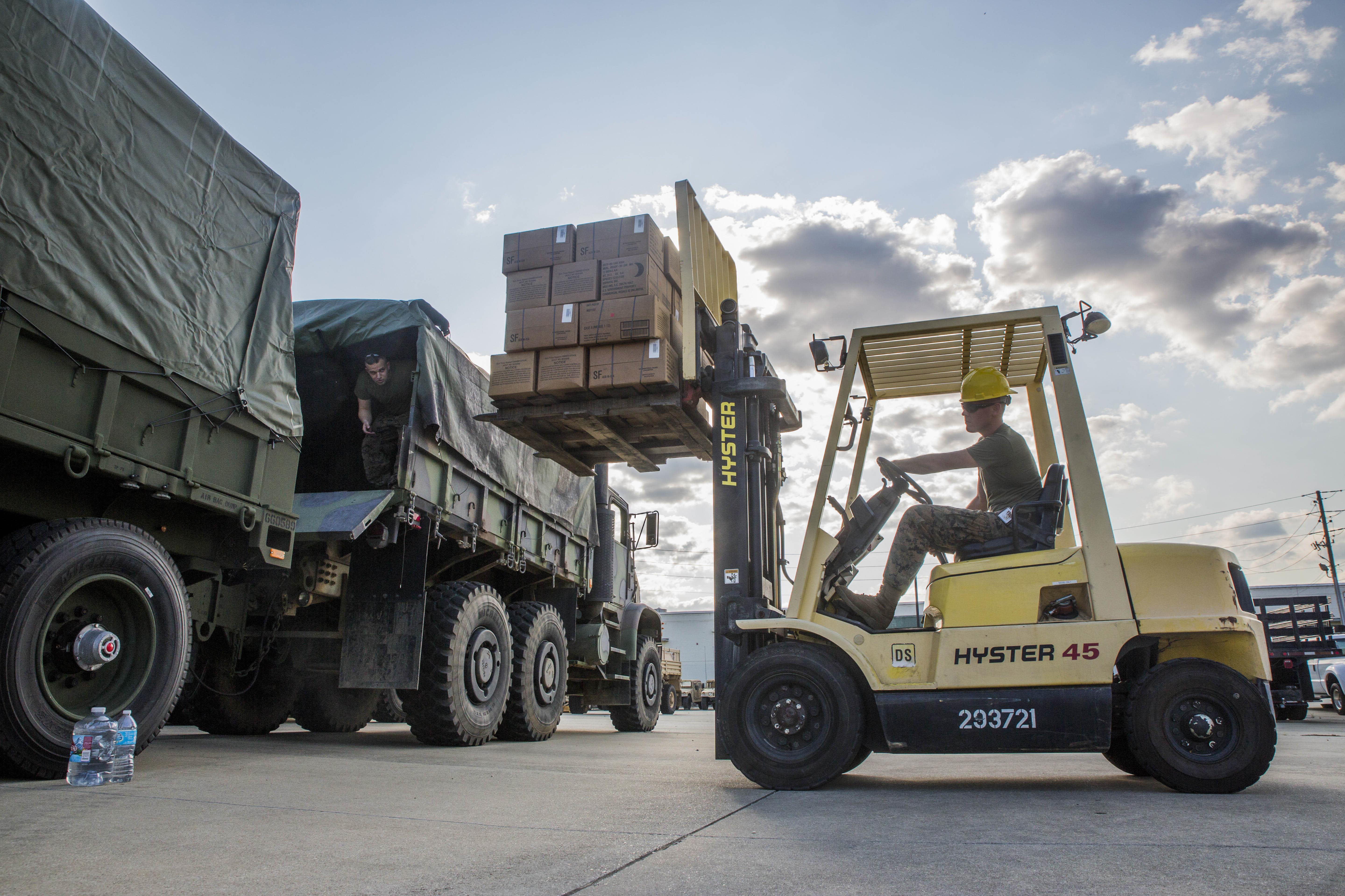 A forklift moves a pallet of boxes into the back of a truck