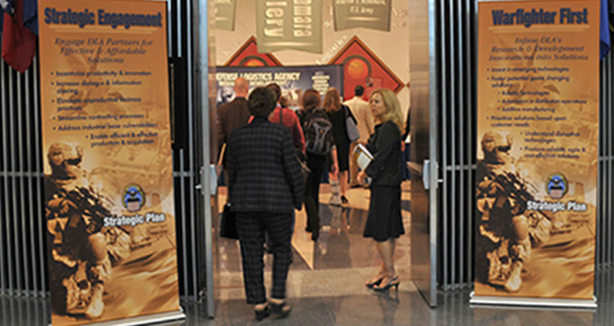 People enter a presentation space flanked by banners