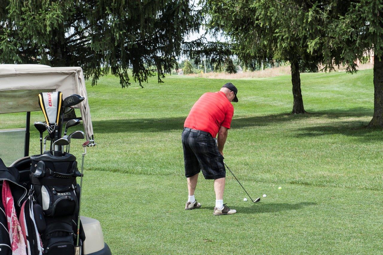 Guy in red shirt golfing with golf cart close to camera shot