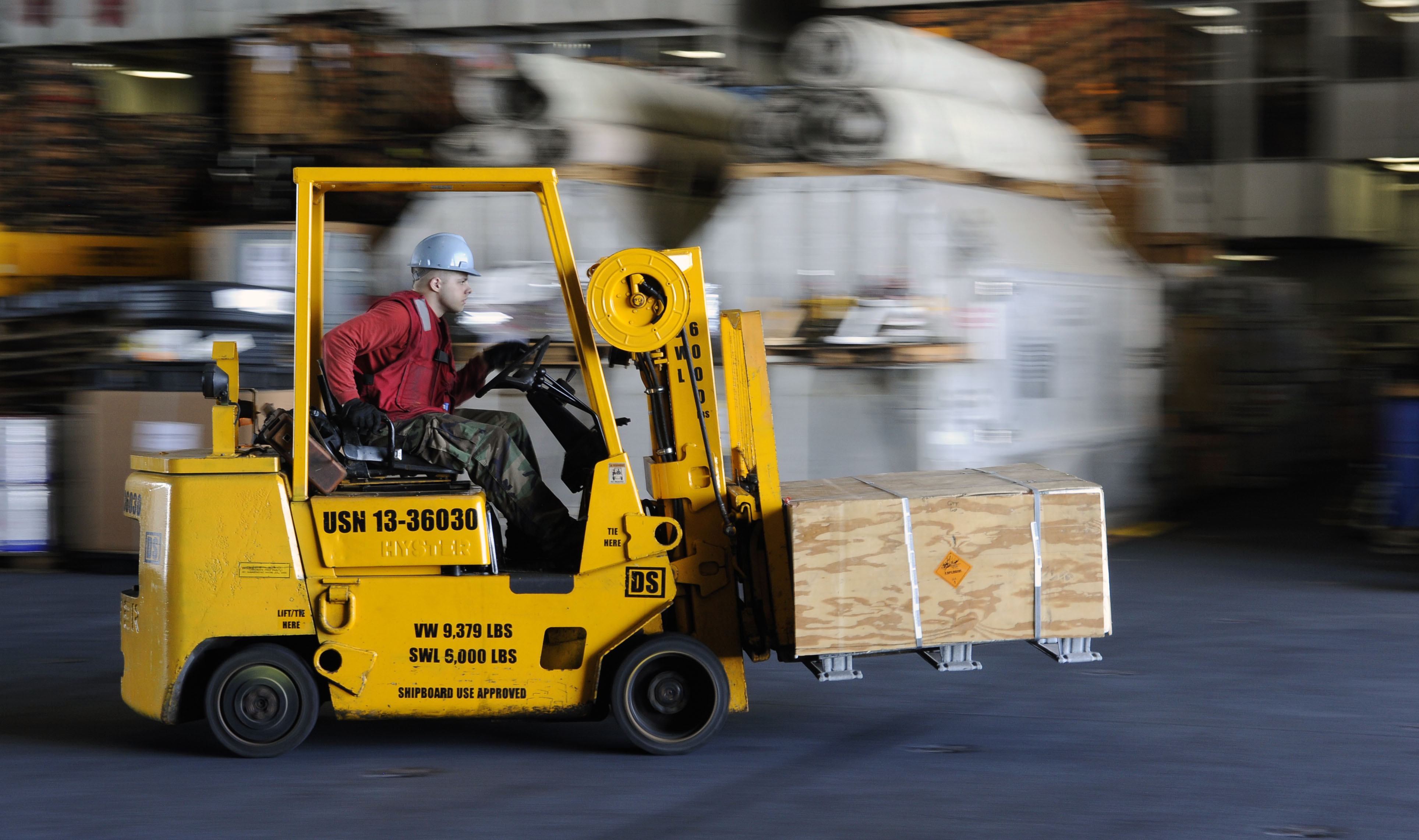 A forklift moves through a warehouse