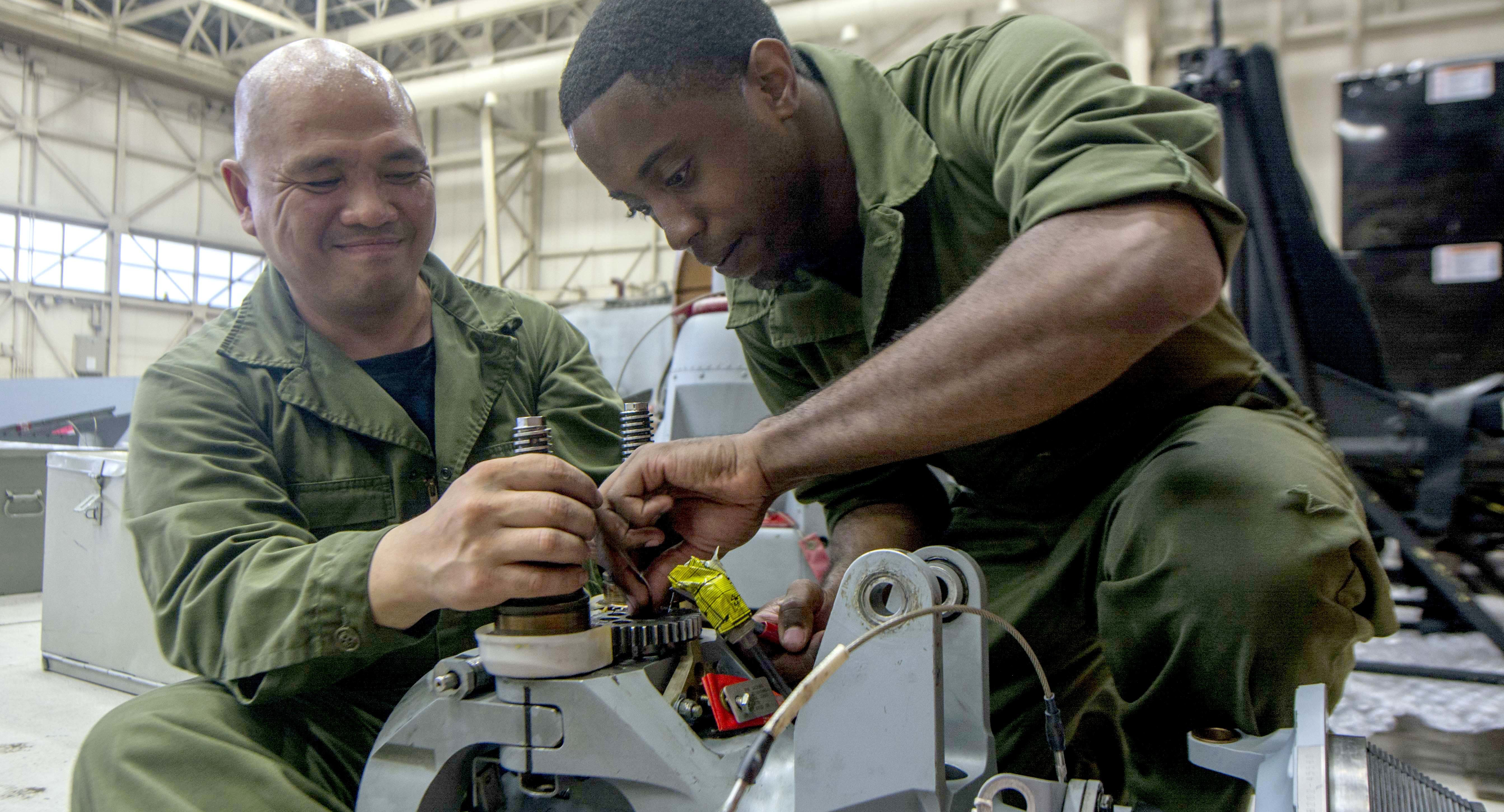 Navy mechanics work on a MH-60R Seahawk helicopter